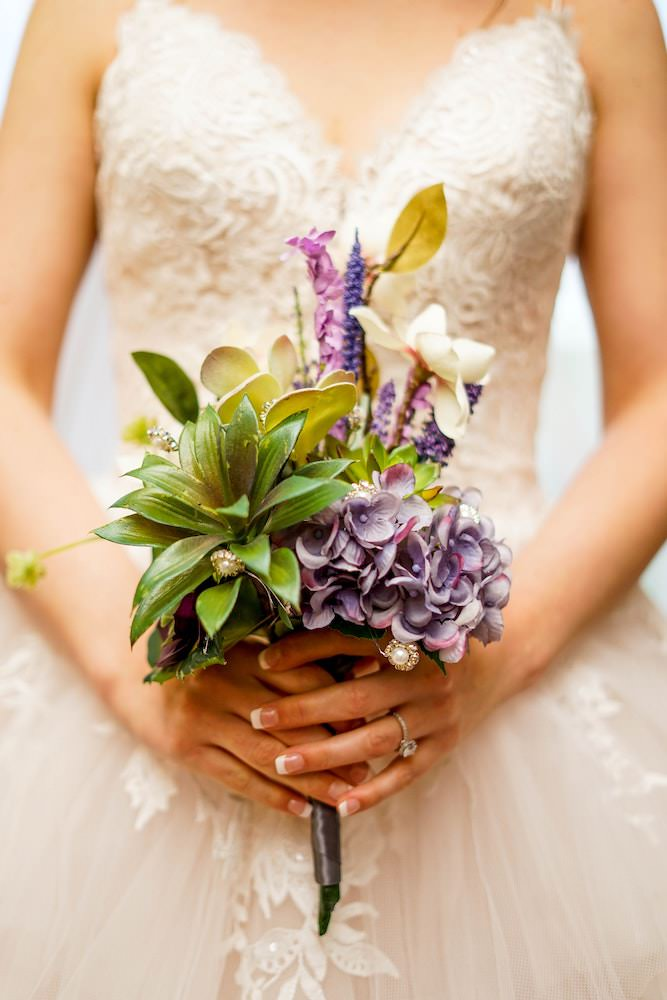 Bride holding bouquet of flowers on her wedding day at Old Lan Farmhouse